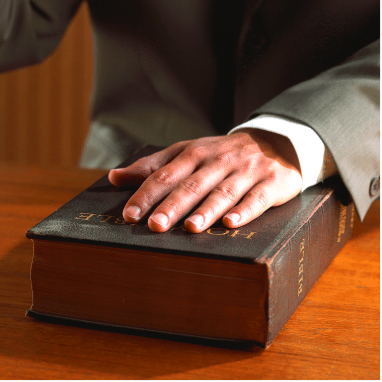 Hand on a bible being sworn in as an Expert Witness