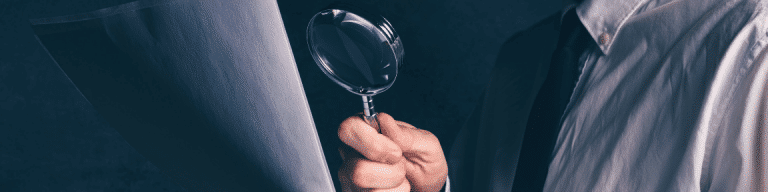 Man using magnifying glass to examine Expert Witness report